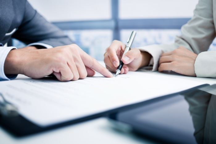 close-up of two business people's hands signing a contract